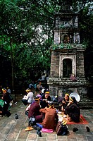 Group of people eating food in front of a temple, Vietnam