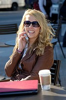 girl/woman 20 yrs on cell phone at cafe/coffee shop with coffee and laptop computer, sunglasses, city, urban, metropolitan, smiling, happy, street, tr...
