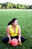Latino woman holding soccer ball - football