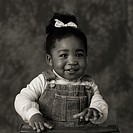 Black and white portrait of a young African American girl in overalls and a bow in her hair.