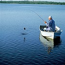 A senior man in a row boat reels in his catch.