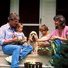 Father, mother, son, and daughter sitting on the front porch with their Cocker Spaniel shaving ears of corn.
