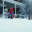 African-American father and son shovel the snow off their walkway as mother and daughter watch from the porch.