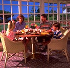 A mother, father, son and daughter sitting at a table having breakfast together.