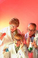Portrait of two female and one male mad scientists all holding beakers with colored fluid, wearing glasses and white lab coats.
