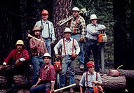 Portrait of loggers standing and sitting on large logs with their equipment near Placerville, California.