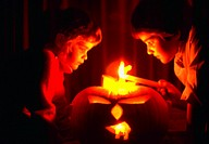 Two children lighting a jack-o-lantern at Halloween.
