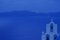 Evening distant view of Santorini, Greece with a dark blue skyline and a white chapel in view.