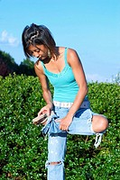 Dark skin teen girl, at a park, examining her shoes