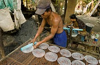 Man rolling out rice paper to dry as woman makes it. Don Teav, Battambang province. Cambodia