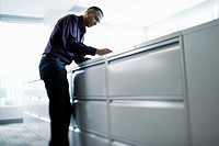 Businessman Leaning on Filing Cabinets