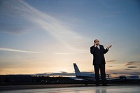 Executive Using Cell Phone on Airport Tarmac