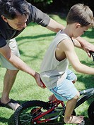 Man Helping Little Boy Ride Bicycle