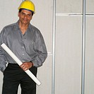 Building Contractor in Hard Hat Holding Blueprints