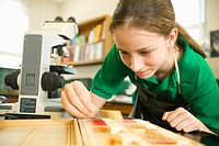 Teenage Girl Examining Slides and Using Microscope