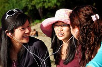 3 asian girls laughing together listening to music