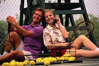 Happy Couple Telephoning from Tennis Court