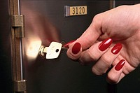 Hand Turning Key to Safe Deposit Box