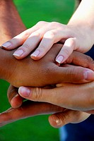 group of young adults stacking hands on top of each other