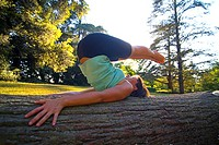Young woman exercising on tree trunk