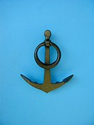 Metallic anchor on light blue background
