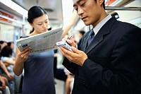 Businessman Using PDA on Subway