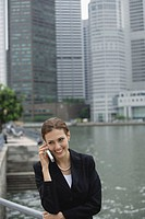 Businesswoman using mobile phone, river and buildings in the background
