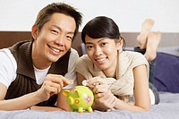 Couple lying on bed, putting coins in piggy bank, looking at camera