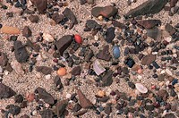 Wind-abraded stones and crystals on a desert surface  The dark angular stones are known as dreikanter stones, so-called because they have a pyramidal ...