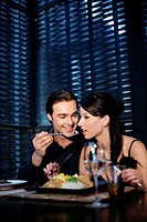 Man feeding his girlfriend while eating in a restaurant