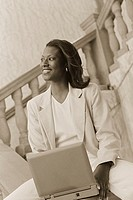 Businesswoman on Bannister with Laptop