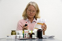 elderly woman, older, elder, woman, medicines, reading, glasses, packing addition, slip of paper, application, pills,