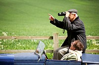 Man using binoculars while sitting in the car