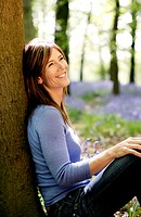 Woman smiling while leaning against a tree