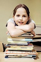 Girl resting on a stack of books