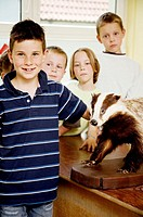 Boys and girls posing with model bear in the classroom
