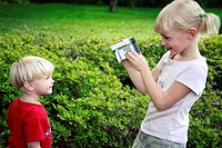 Girl recording the images of little boy
