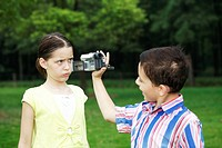 Boy recording images of girl making a face
