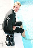 Businessman soaking his legs inside the swimming pool