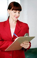 Businesswoman writing on clipboard (thumbnail)