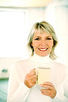 Woman holding a glass while smiling at the camera