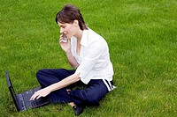 Woman talking on the mobile phone while using laptop in the park