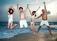 Men and women jumping happily on the beach