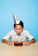 Boy with party hat blowing the candle on his birthday cake