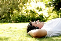 Man lying on the grass listening to music on the headphones