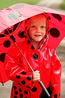 A child with matching raincoat and umbrella