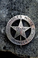 A distinctive circle and star Texas Ranger badge belonging to Charles Moore.