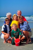 A colorful family portrait of three generations posing on the beach.