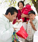 Parents with son 8-9 and newborn baby 3-6 months, man looking into bag