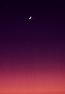 Pink and purple sunset sky with crescent moon